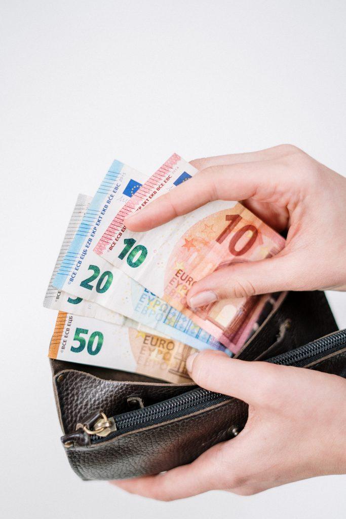 Egy pénztárcában számolja egy kéz a pénzt