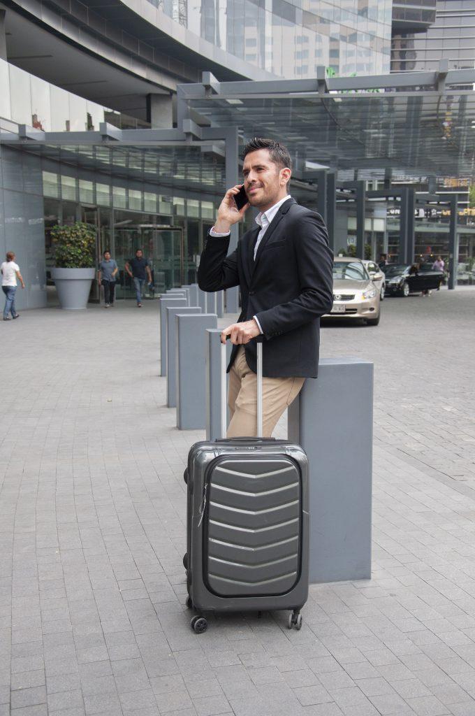 Üzletember telefonál miközben egy bőröndöt húz a reptéren